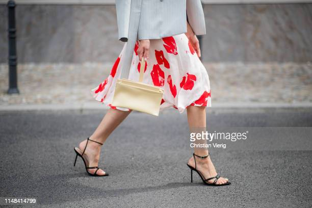 Victoria Nasir is seen red and cream cloroed midi skirt Iris Ink pastell yellow clutch with strap Aesther Ekme shirt keep skies clear from Super Pax...