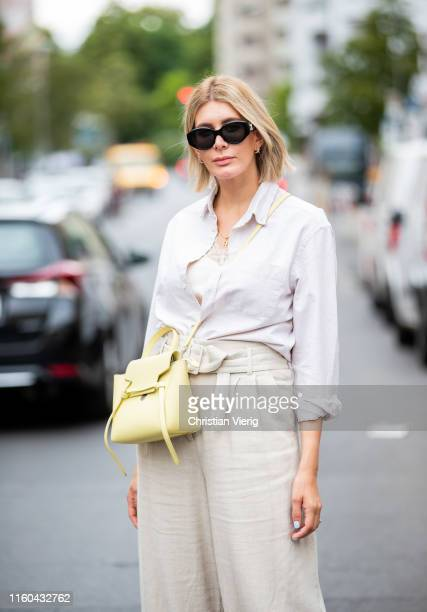 Victoria Nasir is seen wearing beige belted linen trousers HM with vintage Polo Ralph Lauren linen shirt lemon yellow Celine bag on July 06 2019 in...