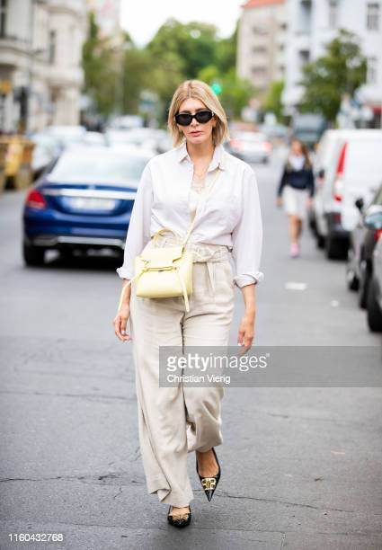 Victoria Nasir is seen wearing beige belted linen trousers HM with vintage Polo Ralph Lauren linen shirt Balenciaga flats lemon yellow Celine bag on...