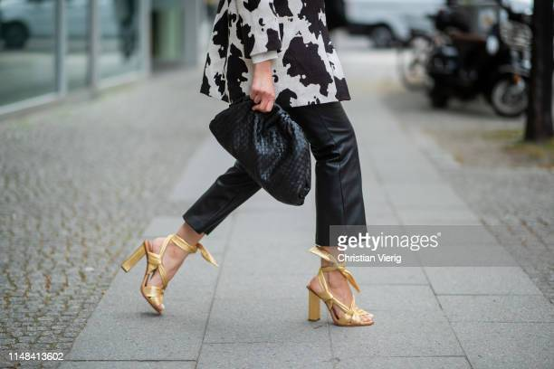 Victoria Nasir is seen wearing belted leather trousers with knit Zara metallic golden wrap sandals Santoni boxy jacket with cow pattern Mango the...
