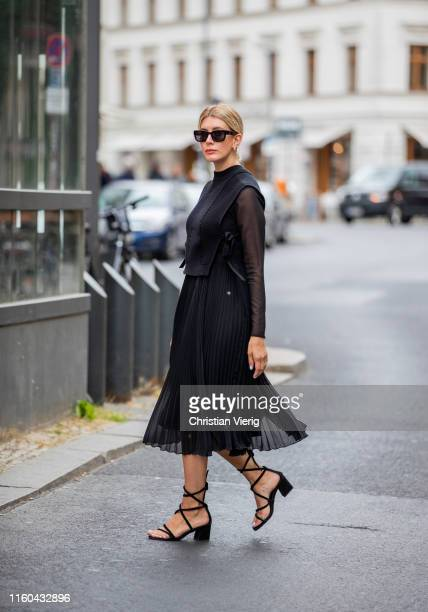 Victoria Nasir is seen wearing black pleated dress with knit slipover Riani black laced up heels Topshop on July 06 2019 in Berlin Germany