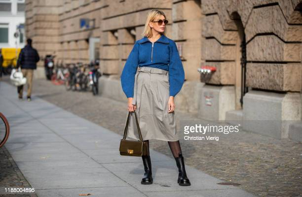 Victoria Nasir is seen wearing grey high waist cargo skirt Tibi blue sweater with zipper Tibi black boots Bottega Veneta sheer tights BV classic bag...