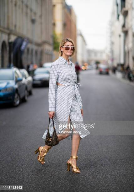 Victoria Nasir is seen wearing light blue checked wrap dress Tibi with vintage Fendi baguette bag golden metallic wraped sandals Santoni cycle...