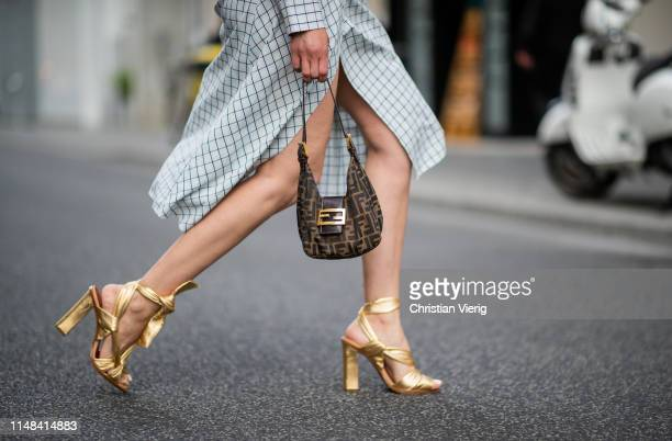 Victoria Nasir is seen wearing light blue checked wrap dress Tibi with vintage Fendi baguette bag, golden metallic wraped sandals Santoni on May 08,...