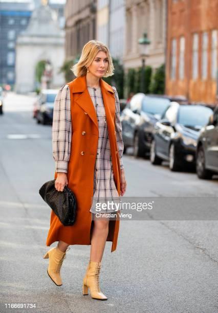 Victoria Nasir is seen wearing orange sleeveless coat, plaid dress, ankle boots, black clutch outside Helmstedt during Copenhagen Fashion Week...