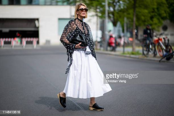 Victoria Nasir is seen wearing white pleated poplin aline skirt COS transparent blouse with polka dots Petar Petrov clogs Zara black the pouch...