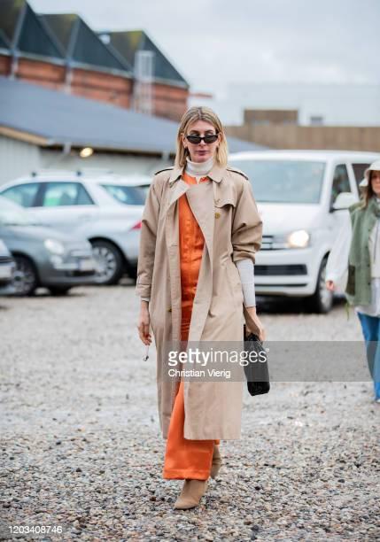 Victoria Nasir seen wearing orange overall trench coat turtleneck outside Baum und Pferdgarten during Copenhagen Fashion Week Autumn/Winter 2020 Day...