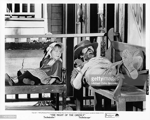 Victoria Paige Meyerink looks at Don Haggerty as he sleeps on a bench with a hat over his eyes in a scene from the film 'The Night Of the Grizzly'...