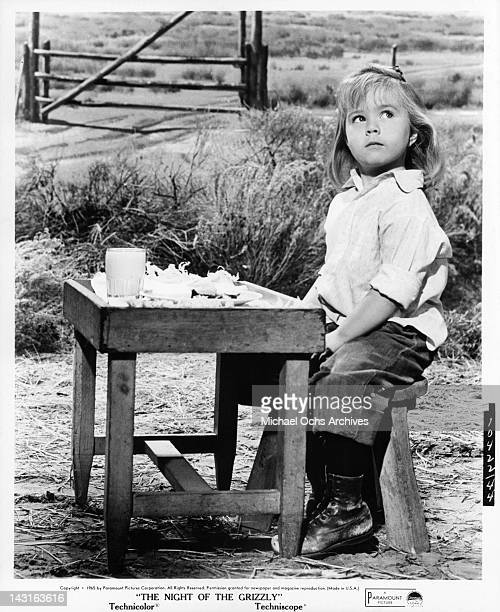 Victoria Paige Meyerink sitting out in a yard at a table made for her size in a scene from the film 'The Night Of the Grizzly' 1966
