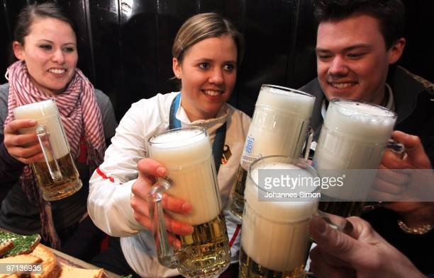 Victoria Rebensburg Olympic gold medal winner cheers with beer mugs beside of her sister Stephanie and brother Dominik during a local reception on...