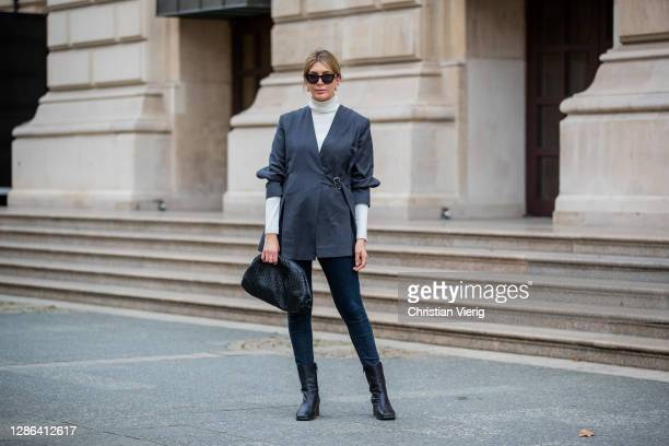 Victoria Scheu is seen wearing Skinny Jeans from Calvin Klein square toe boots from COS white turtleneck Hallhuber Pouch Bag by Bottega Veneta grey...