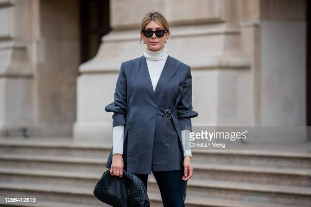 Victoria Scheu is seen wearing Skinny Jeans from Calvin Klein white turtleneck Hallhuber Pouch Bag by Bottega Veneta grey buckled blazer without...