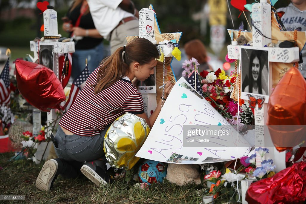 Victoria Seltzer,11, writes a passage on a cross setup in a makeshift memorial in front of Marjory Stoneman Douglas High School in memory of the 17 people that were killed on February 14, on February 21, 2018 in Parkland, Florida. Police arrested 19-year-old former student Nikolas Cruz for killing 17 people at the high school.