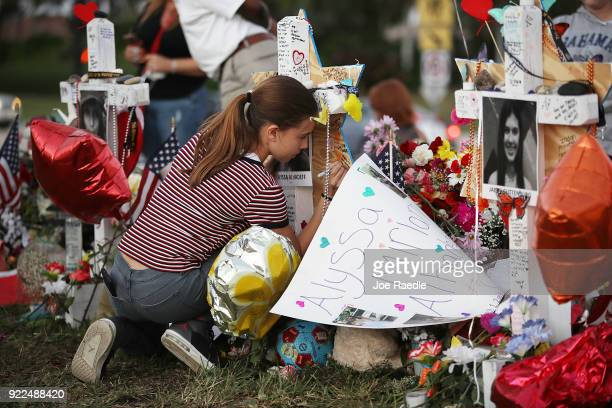 Victoria Seltzer writes a passage on a cross setup in a makeshift memorial in front of Marjory Stoneman Douglas High School in memory of the 17...