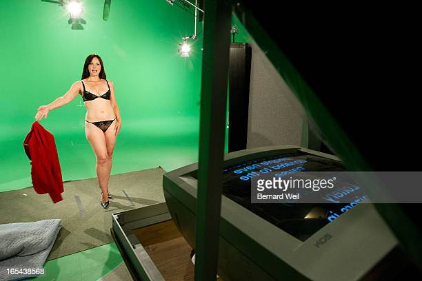 Victoria Sinclair one of the stars of the Naked News slowly strips down while reading from a teleprompter in fron of a green screen A 'newsroom' is...