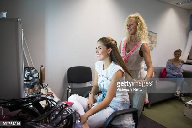 Victoria Swarovski gets her hair done backstage as her sister Paulina Swarovski watches during the behind the scenes visit ahead of the 5th 'Let's...