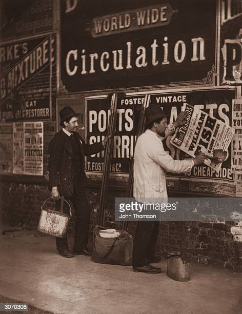 Victorian bill stickers paste placards advertising Madame Tussaud's waxworks museum in London. Original Publication: From 'Street Life In London' by...