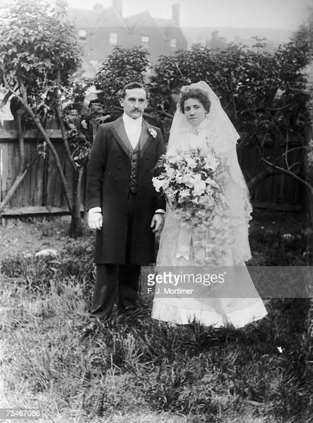A Victorian bride and groom pose in the garden 1890s