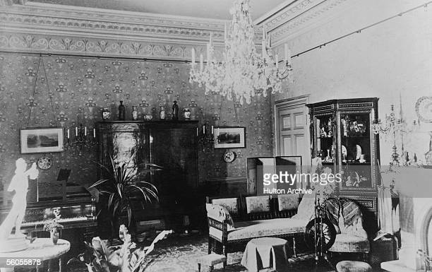 A Victorian drawing room with piano chandelier and ornate floral wallpaper circa 1850