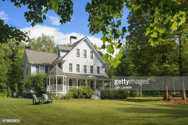 victorian home with lawn and large front porch in summer - ファームハウス ストックフォトと画像