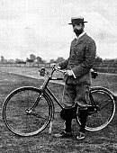 Victorian image of a man in plus fours and a boater stood besides his bike; from The Navy and Army Illustrated 1899
