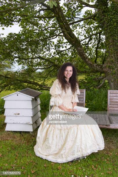 victorian lady reading a book in her garden - long dress stock pictures, royalty-free photos & images
