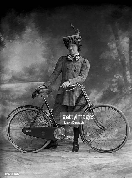 A Victorian lady wearing plus fours poses beside her bicycle