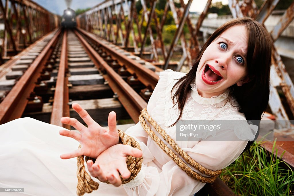 Victorian maiden tied to train tracks screams as engine approaches : Stock Photo