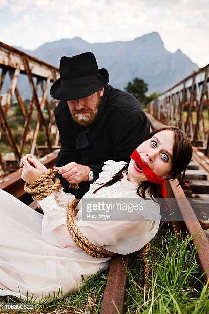 Victorian melodrama as villain ties terrified maiden to railway track