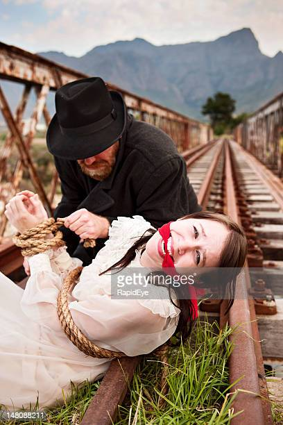 Victorian melodrama as wicked villain ties maiden to railroad tracks