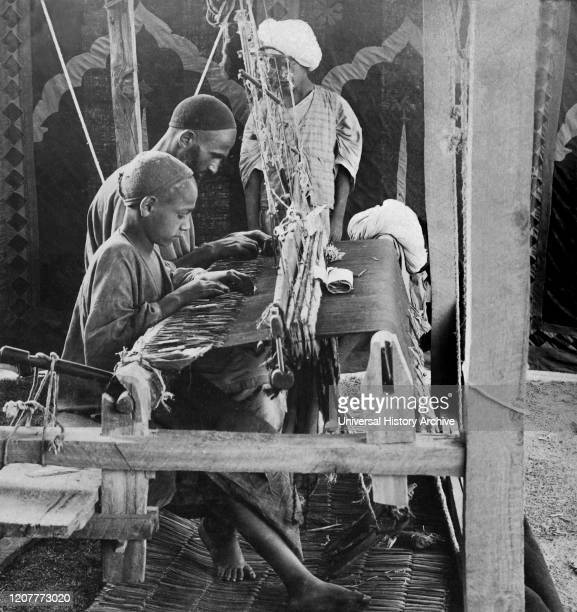 Victorian stereoview card from circa 1900, historic social image. Humble shawl weavers, a father and son working together; Kashmir, India.