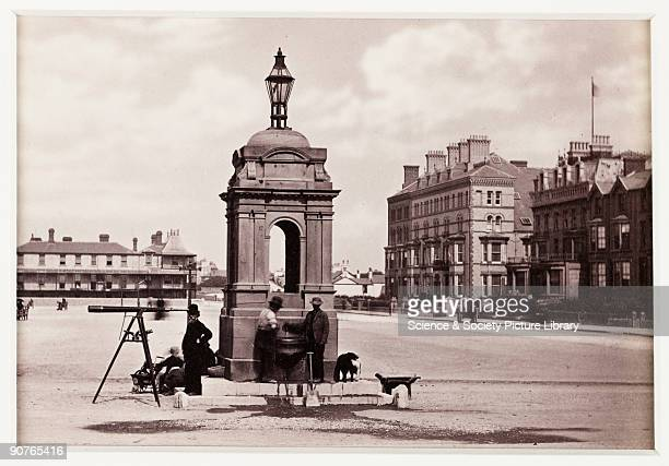 Victorian street scene on the front at the coastal resort of Rhyl in North Wales Two men possibly labourers judging by the shovel and wheelbarrow use...