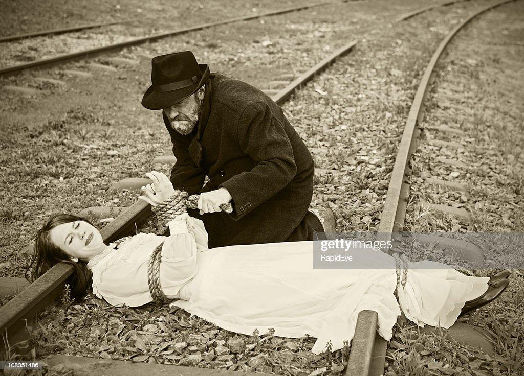 Victorian vignette of villain tying maiden to railroad : Stock Photo