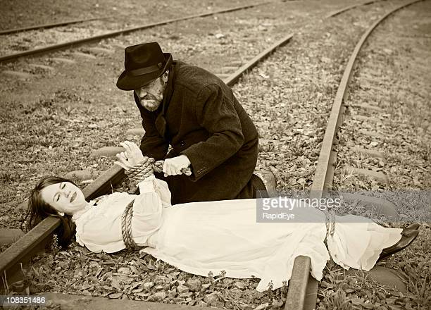 victorian vignette of villain tying maiden to railroad - bound woman stock photos and pictures