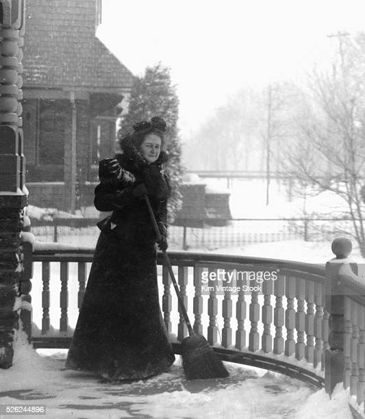Victorian woman sweeps snow off her porch ca 1900