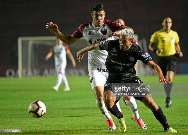 Victorio Ramis of Argentina's Argentinos Juniors and Lucas Acevedo of Argentina's Colon vie for the ball during the Copa Sudamericana last 16...