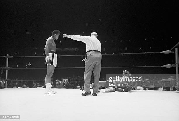 A victorious Cassius Clay stands at attention over his fallen foe Texas challenger Cleveland Williams as referee Harry Kessler points out a neutral...