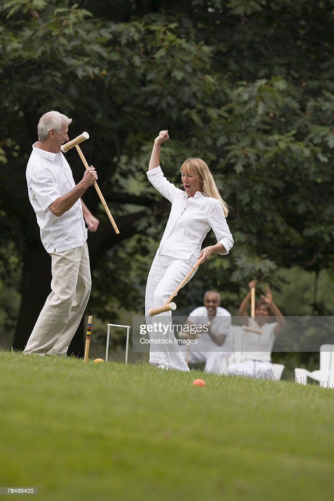 Victorious couple playing croquet : Stockfoto
