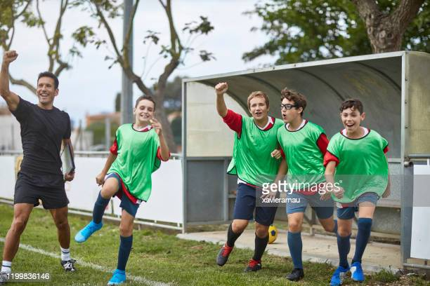 victorious footballers and coach cheering from sidelines - soccer competition stock pictures, royalty-free photos & images