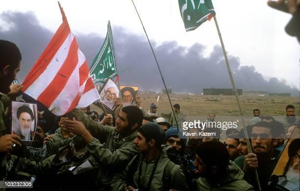 Victorious Iranian Revolutionary Guards burn a US flag in AlFao Peninsula Iraq 15th February 1986 Smoke rises over the Iraqi oil installations...