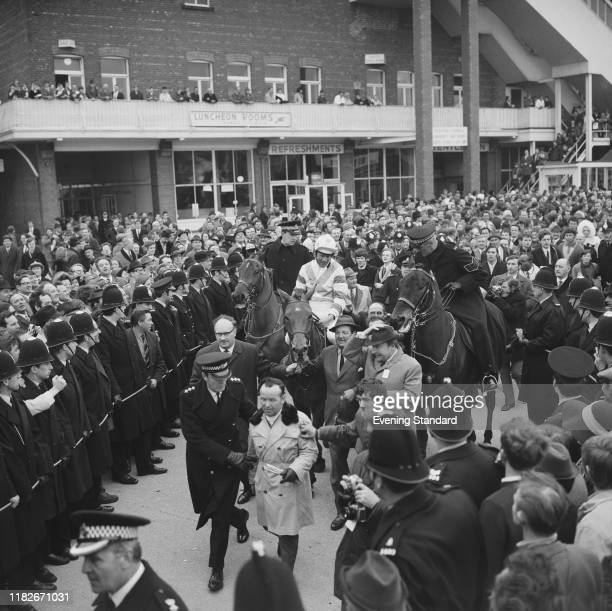 Victorious Irish jockey Pat Taaffe rides in the racehorse Gay Trip through cheering crowds of spectators after finishing in first place to win the...