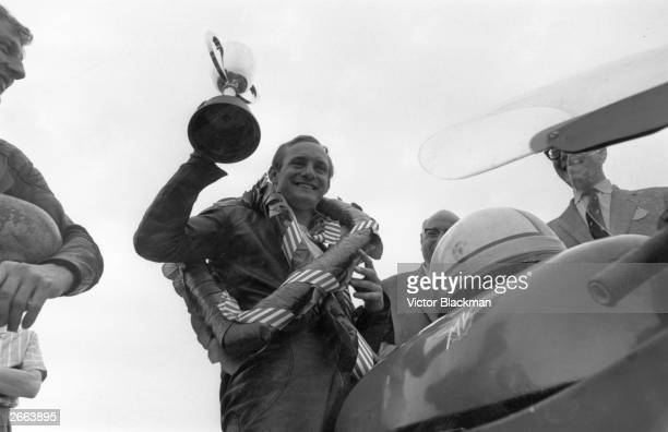 Victorious motorcyclist Mike Hailwood astride his MV Agusta motorbike at Silverstone Race circuit.