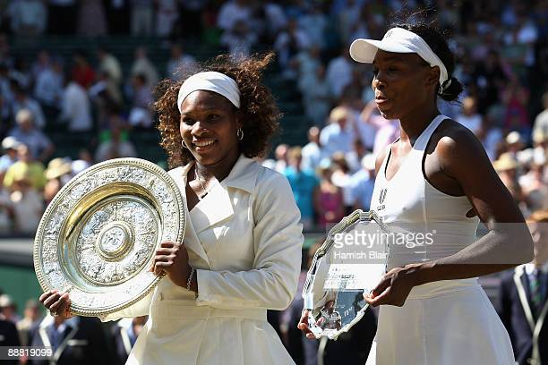 A victorious Serena Williams of USA stands alongside sister Venus Williams of USA after the women's singles final match on Day Twelve of the...