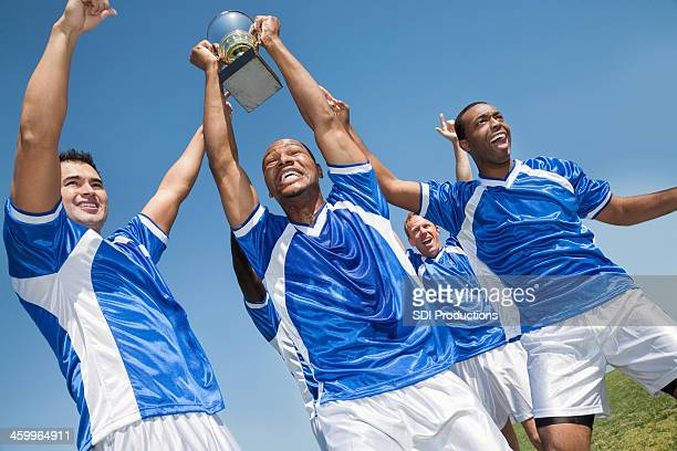 victorious soccer team holding trophy and celebrating win - international soccer event stock pictures, royalty-free photos & images