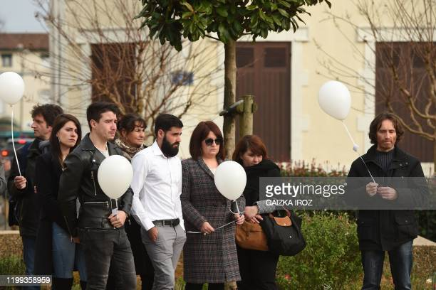 Victor's father Jean-Luc Faget and relatives hold white balloons at the city hall of Dax, southern France, on January 8 during a ceremony in tribute...