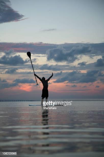 ビクトリーは海のスポーツトレンドのパドルボートの夕日