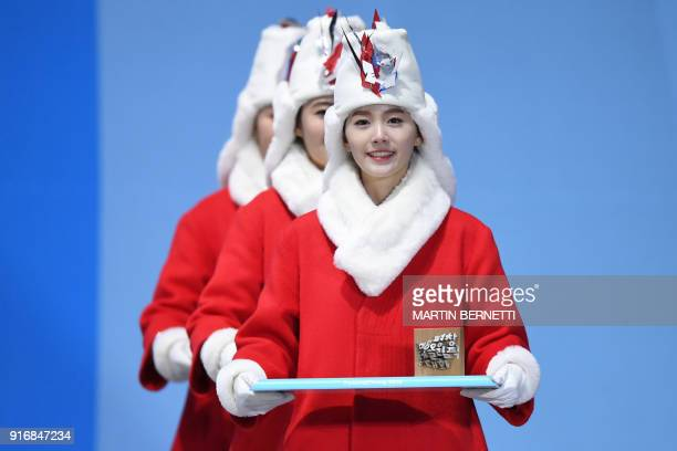 Victory ceremony hostesses arrive to the podium during the medal ceremony for the ski jumping Men's Normal Hill Individual at the Pyeongchang Medals...