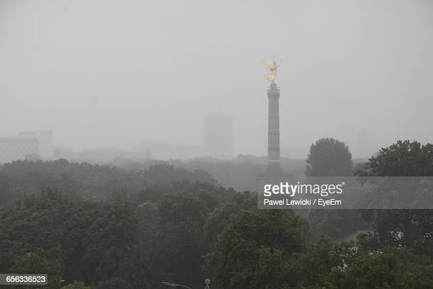 Victory Column By Trees In Foggy Weather