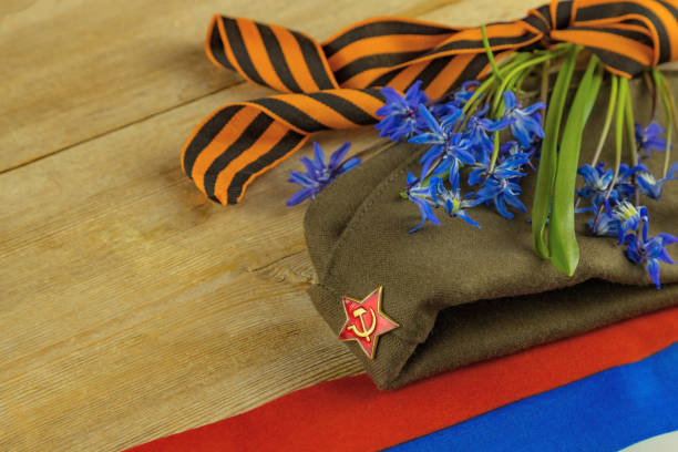 Victory Day 9 may holiday background. George ribbon, Russian flag, flowers, military cap.