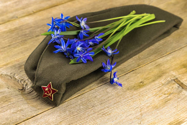 Victory Day 9 may holiday greeting card concept background. military cap and blue spring flowers.